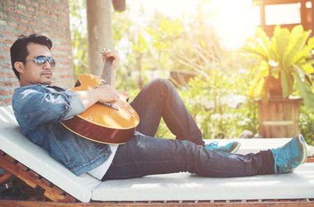 Handsome hipster men practice to play guitar while he is enjoying the relaxing with nature around.