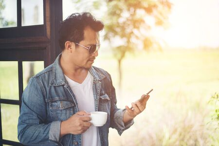 Hipster man holding a cup of coffee and walk in the coffee shop, Relaxing looking at his phone. Stock Photo