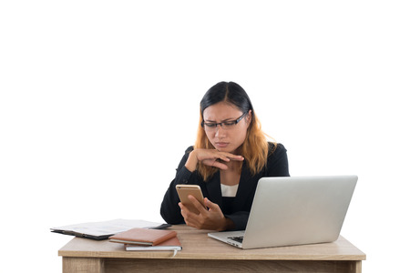 Business woman serious with smartphone while working with her laptop isolated on white background.