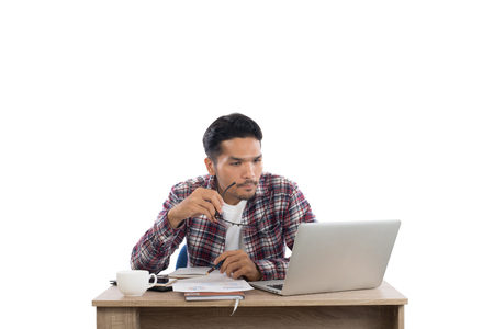 Thoughtful young man  looking at laptop while sitting at his working place isolated on white background. Imagens