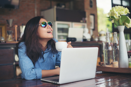 smiled: Pretty young hipster woman sitting in a cafe with her laptop, looked away and smiled happy, Relaxing with holiday, Woman lifestyle concept. Stock Photo