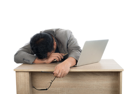 Businessman sleeping next to his laptop computer with white background. Imagens - 77500965