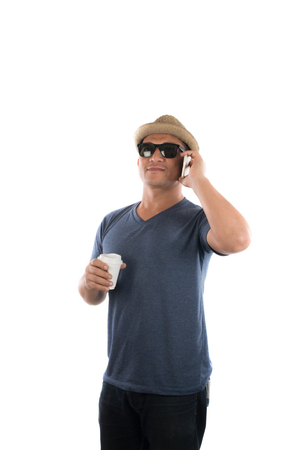 Handsome hipster young man in hat and sunglasses standing and talking on mobile phone over white background.