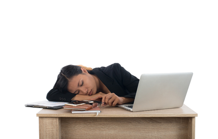 Young business woman tired with her work fall asleep at her desk isolated on white background. Imagens