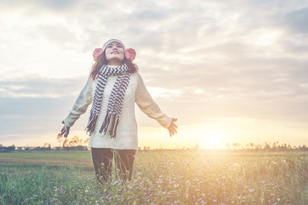 Young girl spreading hands and joy with nature while winter time at sunset background. Stock Photo