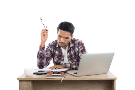 Thoughtful young man holding pen looking at notepad while sitting at his working place. Imagens - 77500989