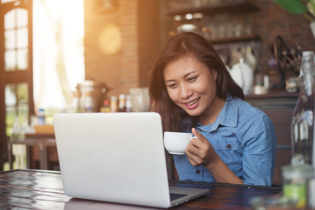Beautiful young hipster woman sitting in a coffee shop, relax and play with her laptop, find information on free time, happy and fun. Lifestyle concept.
