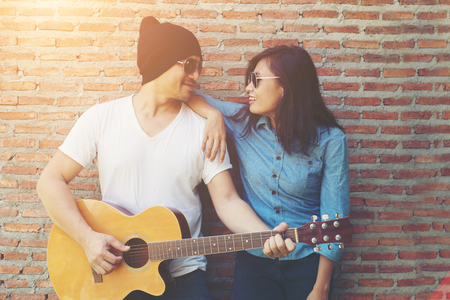 Hipster couple is hugging, looking away and smiling while standing outdoor playing guitar against brick wall, Dating spent great time together. Imagens - 77500997