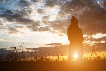 Silueta de mujer de pie en el campo durante la puesta de sol.