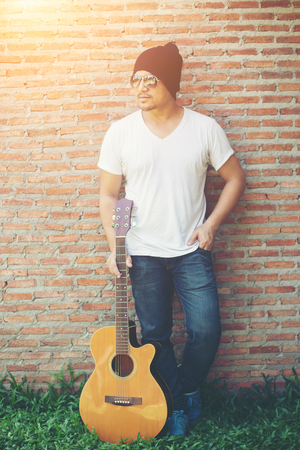 Handsome guy standing holding guitar against the brick wall posing look away. Relaxing holiday.