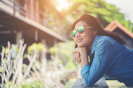 Portrait of  young hipster woman relaxing on a balcony on a sunny summer. Smiling enjoy with nature. Imagens - 77500995