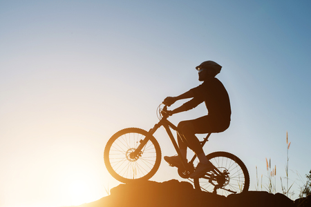 Silhouette of a man on mountain-bike during sunset.
