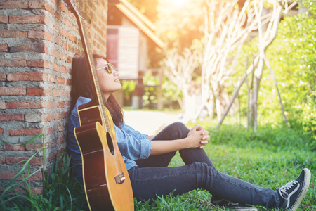 Young hipster girl sitting playing a guitar and singing. Imagens - 77501007