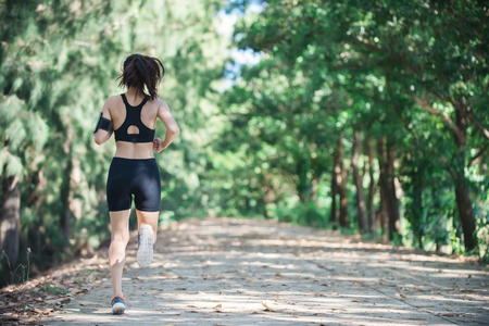 Young fitness woman jogging in park. Imagens