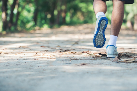 close up foot of young runner man running along road in the park. Stock Photo