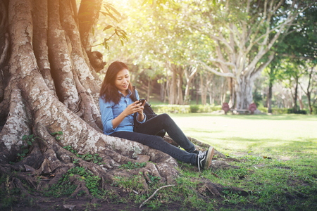 Young hipster woman typing on her phone while sitting at green park. Imagens - 77501018