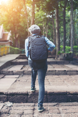 take a history: Young attractive woman tourist with backpack coming to ancient phanom rung temple in thailand.