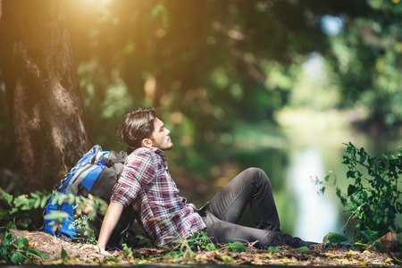 Young tired hiker with backpack sitting on the grass nearby canal resting during hikes. Imagens