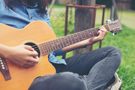 Musician woman and her guitar in nature park, Practice guitar. Imagens