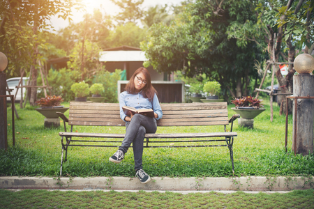 Hipster charming girl relaxing in the park while read book, Enjoy nature around.