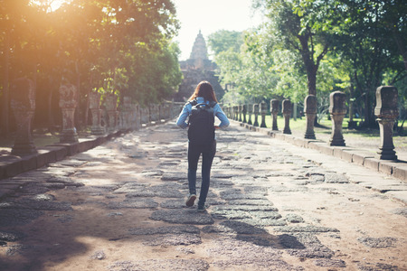 take a history: Rear view of young attractive woman tourist with backpack coming to shoot photo at ancient phanom rung temple in thailand.