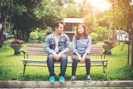 Young smiling couple looking on each other while sitting on bench, Dating time together.