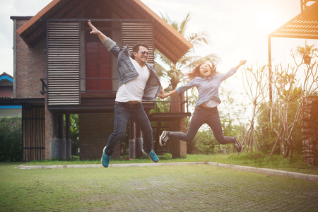 Hipster couple jumping high in the countryside. Couple in love concept. Imagens