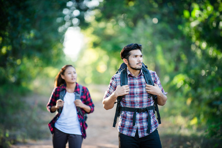 Young couple walking with backpacks in forest. Adventure hikes, Enjoy holidays together, Couple in love.