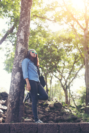 Attractive girl standing against tree, While traveling.