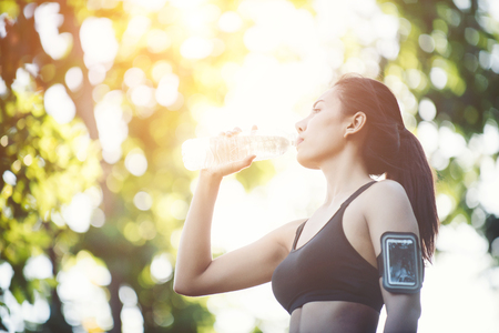 Fitness woman athlete takes a break, Drinking water, Hot day. Country rural road nature background.