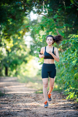 Young fitness woman running on a rural road. Sport woman running,Healthy lifestyle concept. Imagens