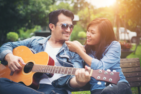 Young couple in love playing acoustic guitar in the park while sitting on the bench together. Imagens