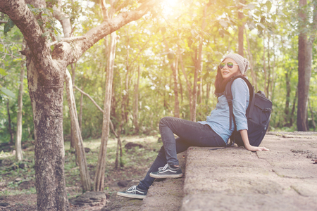 Young attractive woman resting with backpack while going to ancient phanom rung temple in thailand.