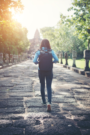 Rear view of young attractive woman tourist with backpack coming to shoot photo at ancient phanom rung temple in thailand.