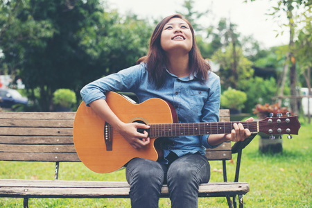 Beautiful young woman playing guitar sitting on bench, Happy time concept.