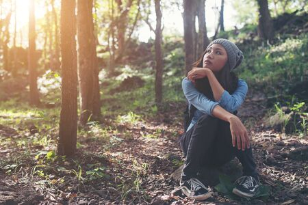 Portrait of a beautiful young  hipster woman in hat, sitting outdoor on the rock of mountain and forest. Imagens