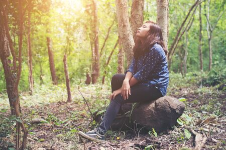 Young hipster woman tried for hike in forest, take some rest setting on the rock looking away to nature. Imagens