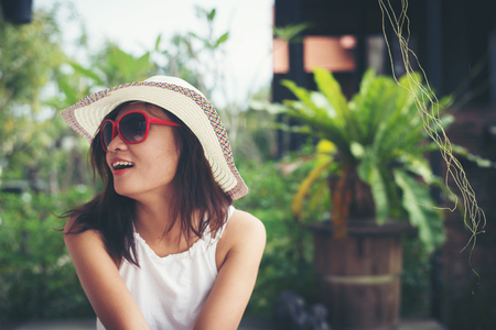 Portrait of charming woman relaxing on the deck chair outdoors with hat and glasses.