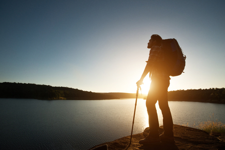 Silhouette of hiker man with backpack in beautiful sunset summer landscape mountain. Imagens