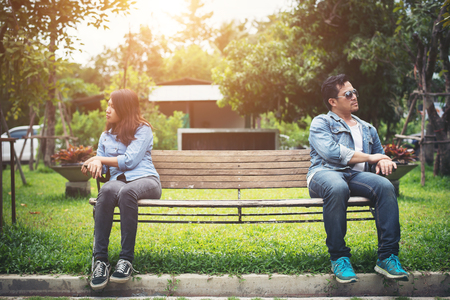 Displeased young couple sitting on bench in park, Couple lifestyle concept.