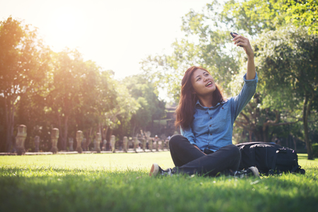 Young hipster woman taking selfie on her phone while sitting at green park. Imagens - 77501042