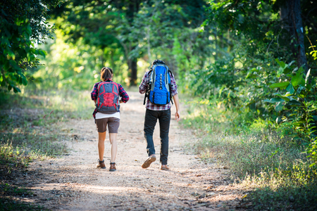 bonne aventure: Young couple walking with backpacks in forest. Adventure hikes, Enjoy holidays together, Couple in love.