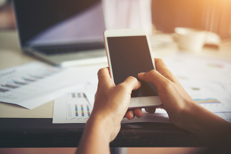 Business woman hands typing on mobile phone while working with her laptop in office.