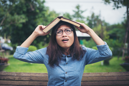 Young hipster woman cover her head with book, afraid of something falling while sitting on bench in the park. Imagens