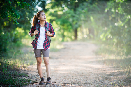 Young woman hiker with backpack walking and smiling on a country trail.