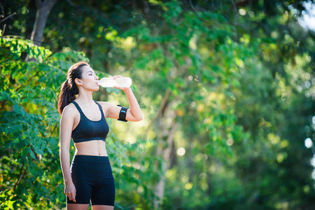 Fitness woman drinking water from bottle. Young woman at rural taking a break during running.
