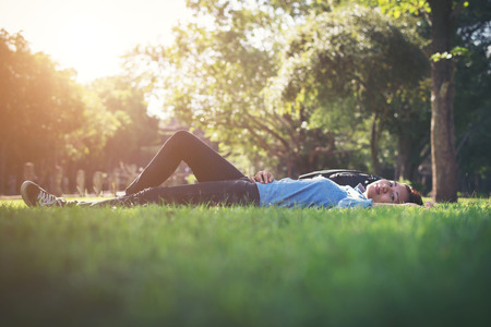 Young hipster woman lying down on grass.