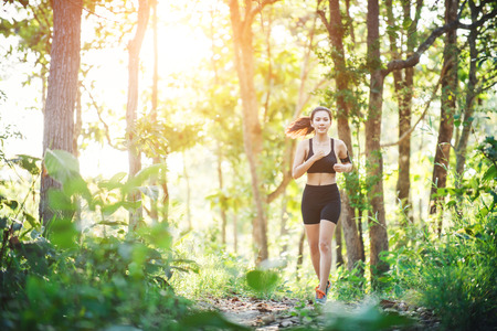 Young woman jogging on rural road in green forest nature. Imagens
