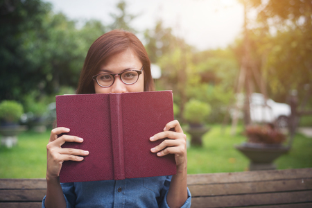 Young hipster girl smiling and covered face by her red book while sitting on bench in the park.