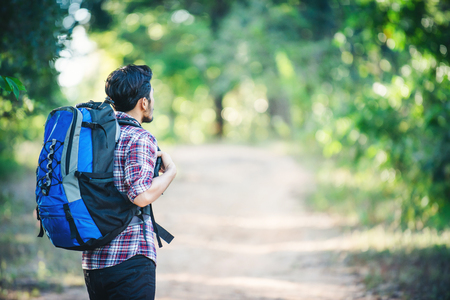 Young hipster man walking on the rural road during hikes on vacation. Adventure hikes. Enjoy holiday.